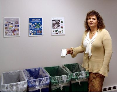 Image of Dawn Inzalaco-Freeman is about to drop a disposable beverage cup into a container for compostables.