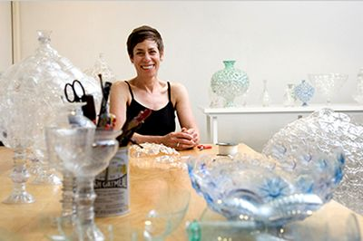 Image of Shari Mendelson in her studio surrounded by vessels made from recycled bottles.