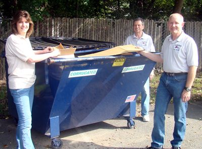 Image of Donna Ricker, Patrick Milligan and David Knizhnik, three industrious employees of the Parsippany Public Library, stand by the container for corrugated cardboard.