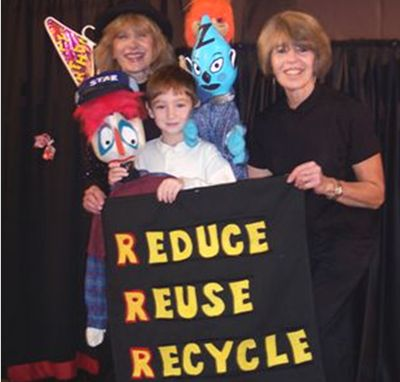 Image of Peppermint puppetry and the three Rs, perfect together—puppeteers Lois and Caroll, along with a student who has just observed one of their programs, pose with three of their puppets (one is made from a plastic bottle) and butterfly scenery made from a hanger and a Mylar balloon