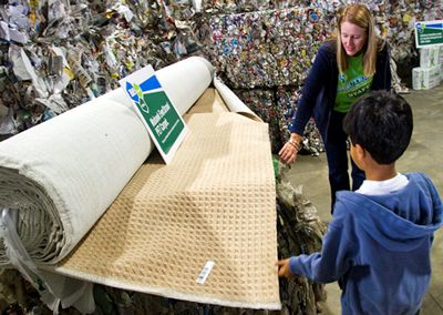 Image of Stephanie Carr, executive assistant at ReCommunity, shows a young Morris County resident the spectrum of the recycling process, including bales of PETE bottles and carpet made from PETE at the October 1 grand opening of the ReCommunity Morris single-stream materials recovery facility.