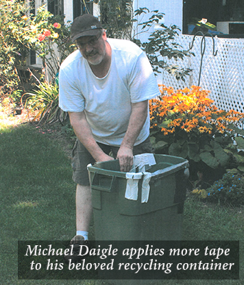 Michael Daigle applies more tape to his beloved recycling container