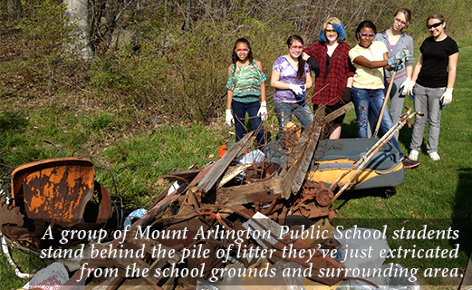 A group of Mount Arlington Public School students stand behind the pile of litter they've just extricated from the school grounds and surrounding area.