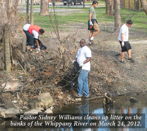 Pastor Sidney Williams cleans up litter on the banks of the Whippany River on March 24, 2012.