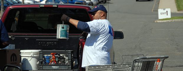 image of examining a paint can taken from a pickup truck.